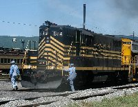 Nickel Plate 514, a diesel-electric locomotive built in 1958, prepares to pull a train out of Scranton.  The locomotive is black with yellow stripes.