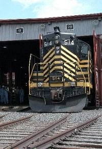 Nickel Plate 514, a dieses-electric locomotive built in 1958, poses half out of the roundhouse doors.  The locomotive is black with yellow stripes.