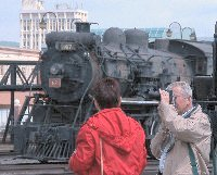 a man focuses on a locomotive out of the picture while a woman looks at a locomotive in the background