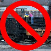 Two children unsafely climb on an historic freight car, with a circle and slash laid over the picture.  Please to not climb.