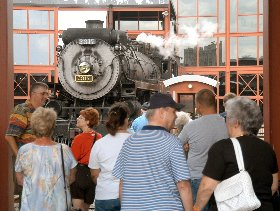 Visitors watch a steam locomotive on the turntable at Steamtown