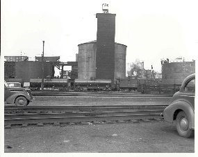 A black and white photo from 1951 showing the sand drying tower with railroad tank cars and period automobiles.