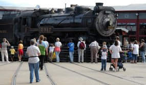 Visitors watch as a steam locomotive turns on the turntable, a rotating bridge