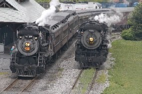 two steam locomotives, both pulling passenger trains, pass the loading platform at Steamtown