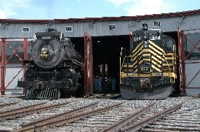 CP 2317 (L) and NKP 514 (R) pose in the doorway of the gray Roundhouse at Steamtown.  The 2317 sports the normal 'steam engine' paint - gray front and everything else black.  The 514 has the black body, but with wide yellow stripes.
