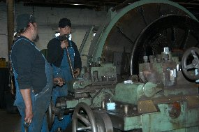 Two of Steamtown's mechanics trim railroad wheels on a large lathe.