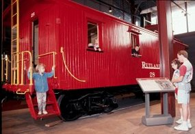 parents read an exhibit panel as a little girl comes down the steps of a red caboose in Steamtown's Technology Museum