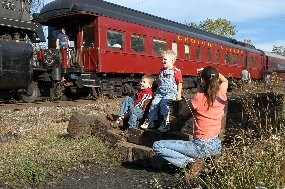 A woman photographs two children with a red passenger car as backgorund.