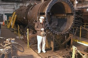 A representative of the volunteer group funding the project stands nest to the bare boiler of the Boston & Maine locomotive 3713.  The locomotive is stripped down to a bare, rust-colored boiler and sits next to a work platform in the Locomotive Shop.