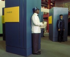 In Steamtown's History Museum, the Life on the Railroad section includes full size multicolor mannequins showing the different jobs of railroading.  The Pullman Porter wears blue slacks, a white jacket, bow tie, and blue cap.  He carries a small stack of sheets.