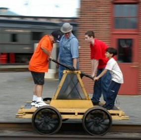 Three children ride on a yellow pump car with a man wearing period overalls and hat.