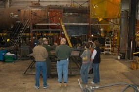 a park ranger tells a small group of visitors about the different projects in the locomotive shop.  behind the group is a stripped down steam locomotive