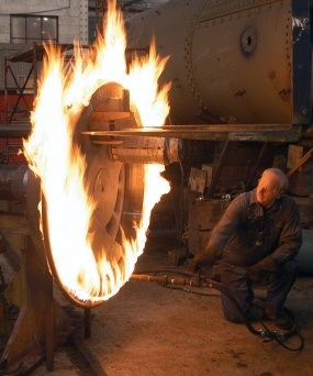 A new tire made of steel is enveloped in flame as it is heated to make it expand.  Once it has expanded 80/1000 of an inch, it can be placed onto the wheel and the, as it cools, it shrinks to fit.
