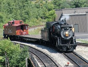 CN 3254, a freight locomotive built in 1917, pulls a flatcar and a Delaware, Lackawanna & Western caboose in the Scranton railroad yard.
