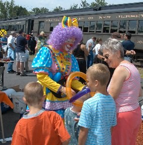 A clown celebrates with children at Carbondale, PA, the train which brought the children is in the background.