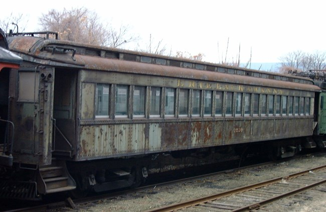 Delaware, Lackawanna & Western Railroad Electric Passenger Trailer #320, rusting, formerly painted in dark green paint and with yellow lettering for Erie Lackawanna