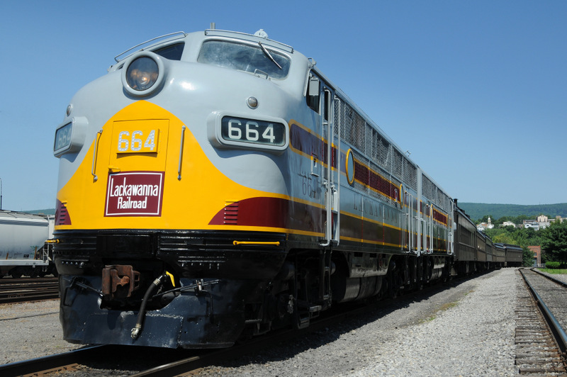 DL&W-painted diesel locomotive, in Lackawanna colors of grey, maroon and yellow, departing Steamtown platform