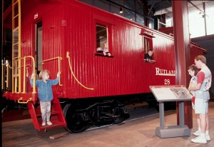 A child steps from a bright red Rutland Railroad wooden caboose on display in the Techhology Museum.