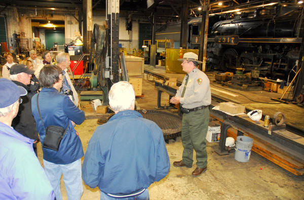 Park Ranger explains locomotive maintenance facilities to visitors on a Locomotive Shop Tour.