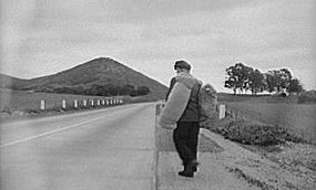 An historic image of a hobo walking along a road with a bed roll slung over his shoulder.