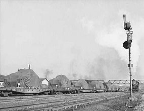 World War II army tanks sit on flat cars covered by tarps in this 1940s photo.