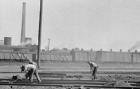 Three workers in a railroad yard.  Historic Photo.