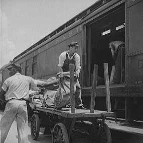 Workers load bags of mail onto a Railway Post Office Car.  Historic Photo