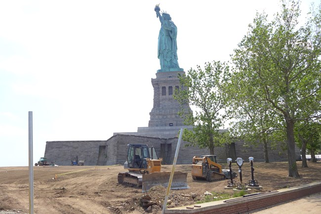A yellow bulldozer sitting on a brown dirt mound in front of the Statue of Liberty.
