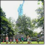 Students playing behind the Statue of Liberty on Liberty Island.