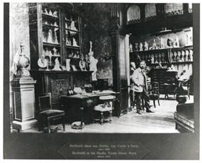 Black and white photo showing a sculptor standing in the midst of an artist studio in 1892.