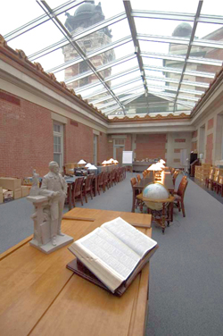 An open book on a table in the foreground, dark wood desks in the rear, brick walls and clear glass roof above.  The Reading Room in the Bob Hope Memorial Library.