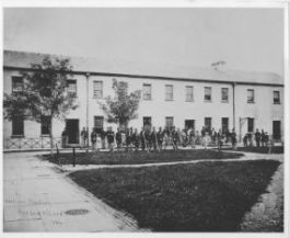 A photograph of soldiers in front of the Garrison's Quarters on Bedloe's Island in 1864.