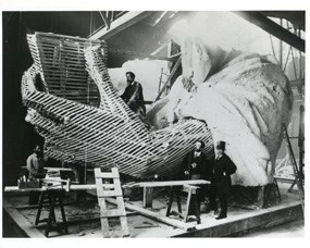 black and white photo showing Lady Liberty's hand under construction.