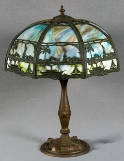 A souvenir lamp. The lampshade depicts the Statue of Liberty alongside buildings, boats, and trees.