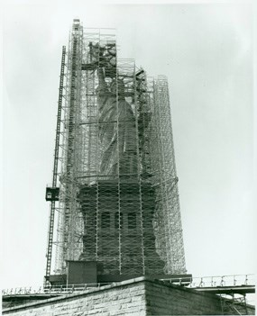 Black and white image showing the Statue of Liberty encased in scaffolding