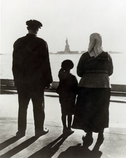 A newly arrived immigrant family on Ellis Island, gazing across the bay at the Statue of Liberty.