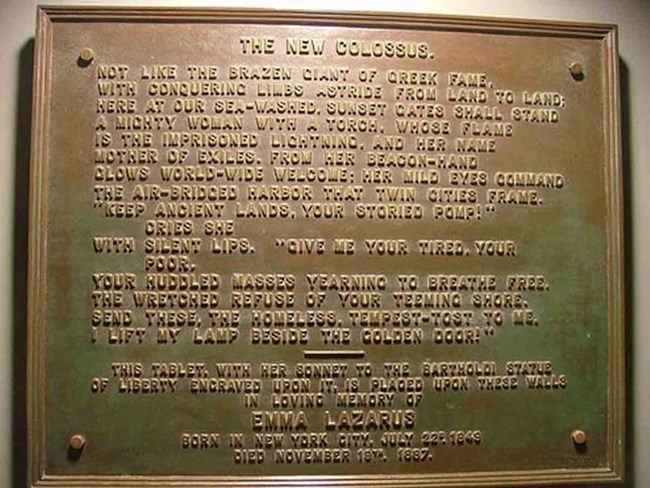 Image of the words of the New Colossus inscribed on a bronze plaque.