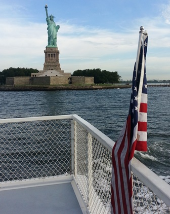 Statue of Liberty with American flag from boat.