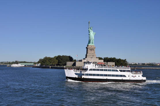 The ferry Miss Liberty passes in front of the Statue of Liberty.