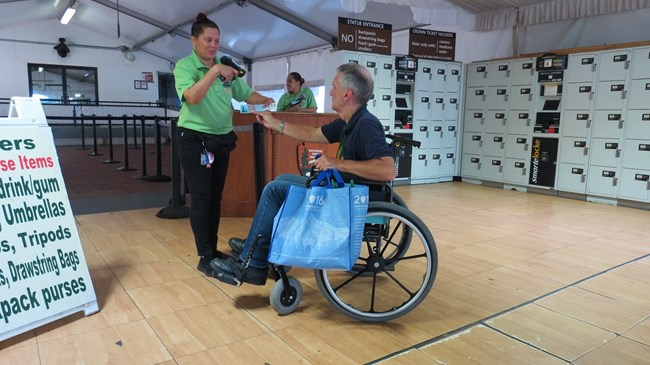 A visitor in a wheelchair is getting his ticket scanned in the screening tent.