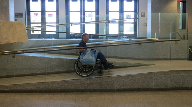 A visiting in a wheelchair is using the inside ramp to go outside onto the Fort Wood level of the monument.