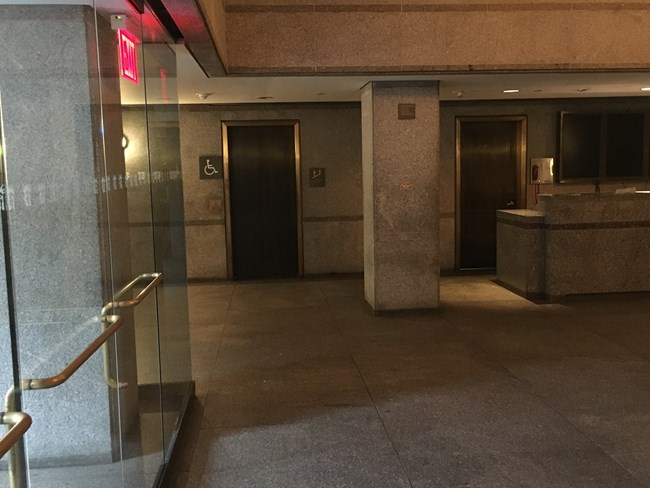 A picture of the first floor elevator door inside the lobby of the Statue of Liberty.