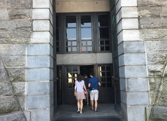 A picture of visitors walking through the large doors of the entrance to the Statue of Liberty.