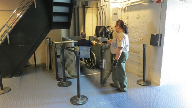 A Park Ranger is opening the door of the wheelchair lift allowing the visitor to exit.
