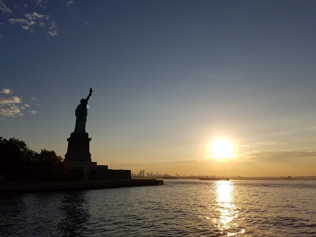 The Statue of Liberty in silhouette with the sun rising in the distance.