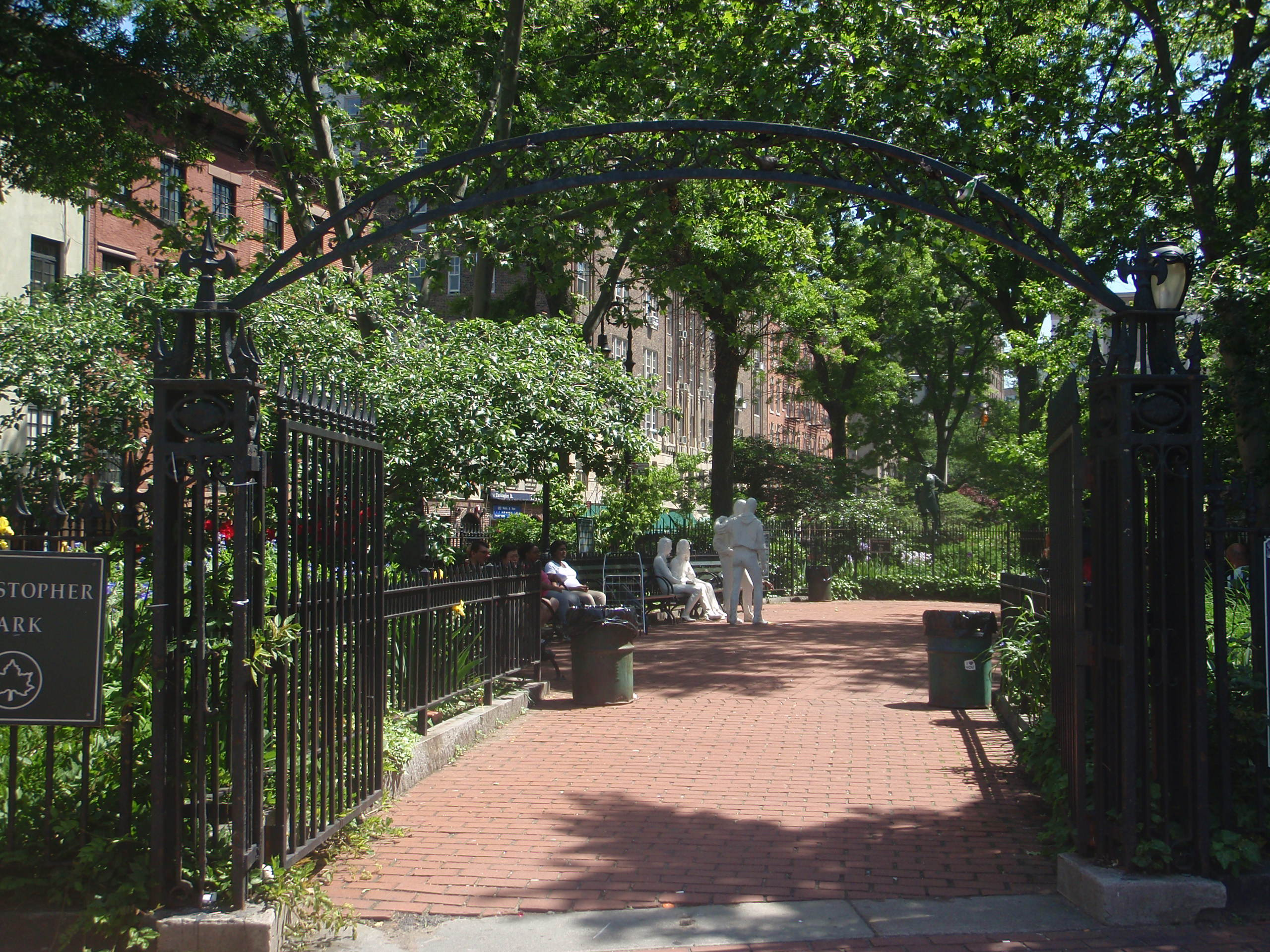 Gated entrance leads to a brick walkway with benches, trees, and several memorials.