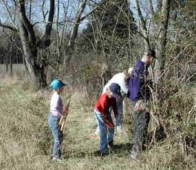 A family of volunteers cutting brush