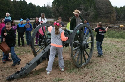 Kids learn to load and fire a cannon with help from a ranger.