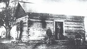 African American soldiers seated and standing in front of a cabin.