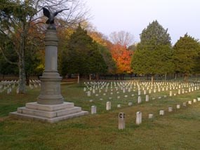 A pillar shaped monument with a bronze eagle on top stands next to rows of national cemetery headstones.